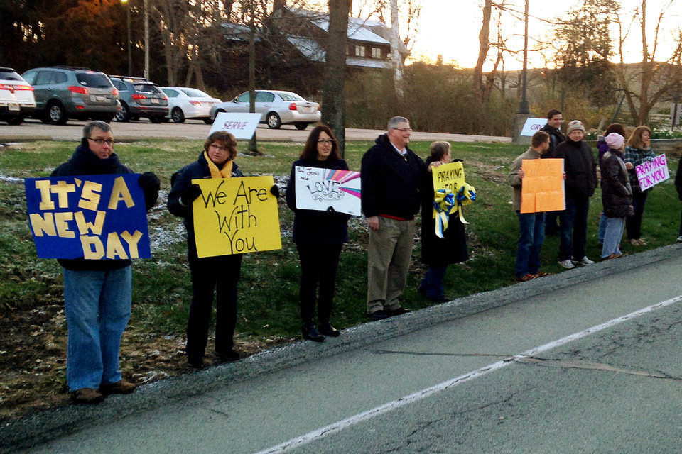 Photo - In this photo made with a cell phone, well-wishers from a nearby church hold signs of support for students returning to Franklin Regional High School, Wednesday, April 16, 2014, in Murrysville, Pa. Classes resumed Wednesday at the Pittsburgh-area high school where authorities said a student stabbed or slashed 21 others and a security guard a week ago. (AP Photo/Joe Mandak)