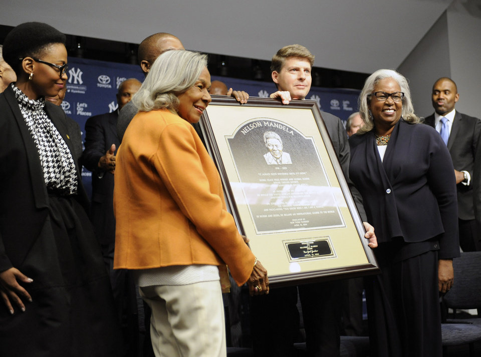 Photo - Mrs. Lindo Mandela, left, looks on as Rachael Robinson, Hal Steinbrenner, and Sharon Robinson, right, pose with a copy of the Nelson Mandela plaque before the Chicago Cubs and the New York Yankees play Game 2 of a baseball doubleheader onWednesday, April 16, 2014, at Yankee Stadium in New York. (AP Photo/Bill Kostroun)