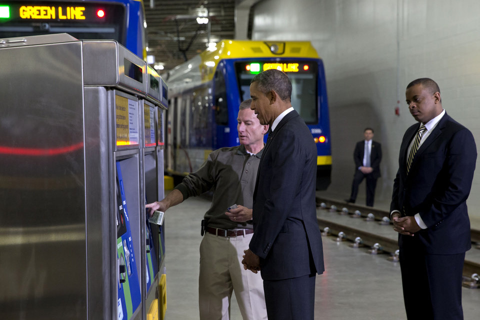 Photo - President Barack Obama and Transportation Secretary Anthony Foxx, right, listen as Mark Fuhrmann, New Start Program Director of Metro Transit, left, shows them a ticket vending machine during a tour of the Metro Transit Light Rail Operations and Maintenance Facility, Wednesday, Feb. 26, 2014, in St. Paul, Minn. In Minnesota Obama is expected to speak at Union Depot rail and bus station with a proposal asking Congress for $300 billion to update the nation's roads and railways, and about a competition to encourage investments to create jobs and restore infrastructure as part of the President's Year of Action. (AP Photo/Jacquelyn Martin)