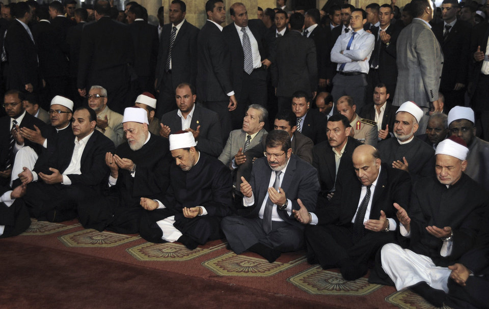 Photo -   FILE - In this Friday, June 29, 2012 file photo, new Egyptian President-elect Mohammed Morsi, third right, prays with Grand Sheik Ahmed el-Tayyib, fourth right, and Grand Mufti Ali Gomaa, third left, at Friday prayers at Al-Azhar mosque, in Cairo, Egypt. Morsi leads prayers at the presidential palace and insists that his portraits must never go up on the walls of every school and government office as it has been customary in Egypt. He was seen crying while listening to a moving sermon last Friday and is refusing to move to the presidential palace, preferring instead to stay at his apartment in a suburb just east of Cairo where he is up every day at dawn to pray at a nearby mosque. (AP Photo/Ahmed Fouad, Egyptian Presidency, File)