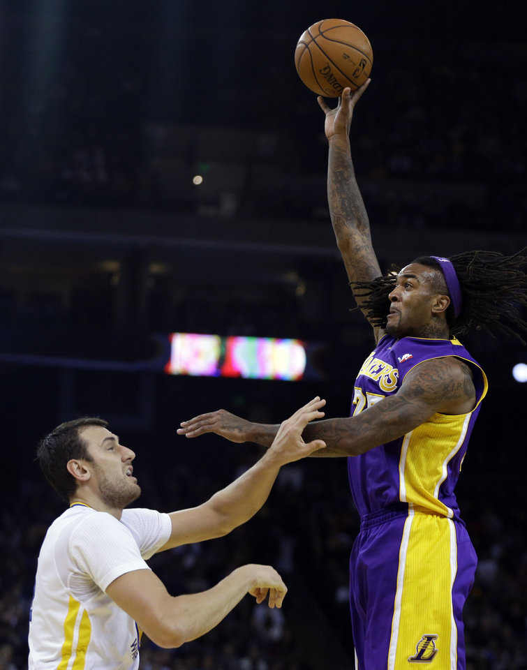 Photo - Los Angeles Lakers' Jordan Hill, right, shoots over Golden State Warriors' Andrew Bogut during the first half of an NBA basketball game Saturday, Dec. 21, 2013, in Oakland, Calif. (AP Photo/Ben Margot)