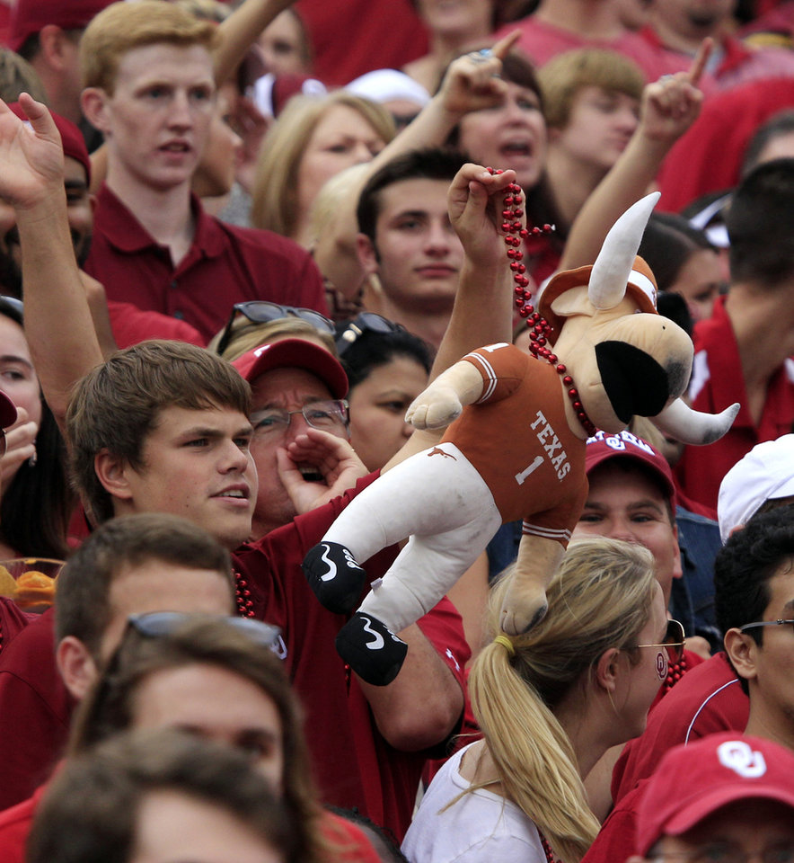 Photo -   An Oklahoma fan holds up a stuffed longhorn during the first half of an NCAA college football game against Texas at the Cotton Bowl Saturday, Oct. 13, 2012, in Dallas. (AP Photo/LM Otero)