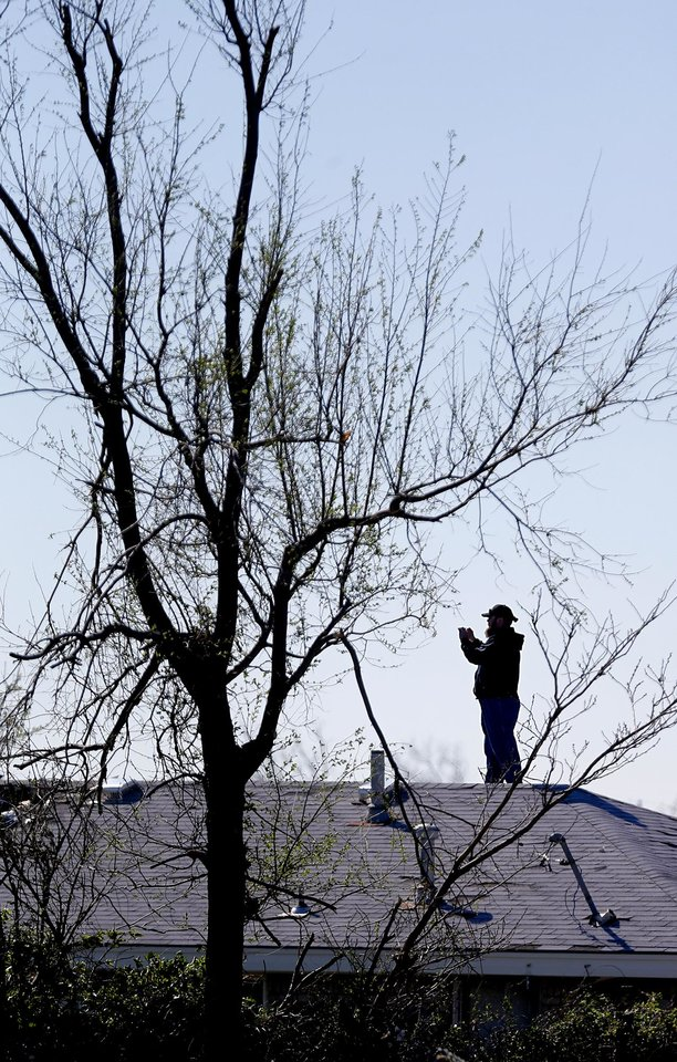 Photo - A home owner stands on the roof to take photos of the storm damage through the neighborhood in Moore, Okla. on Thursday, March 26, 2015. A tornado hit the area on Wednesday evening causing damage in the area.  Photo by Chris Landsberger, The Oklahoman