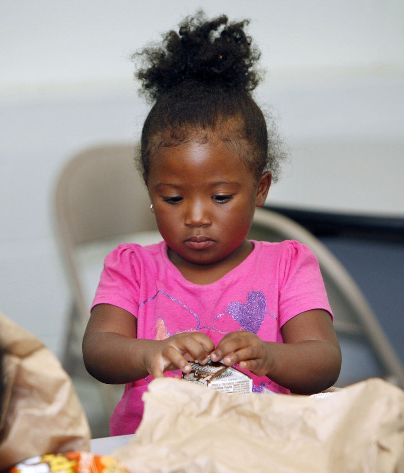 Three-year-old T'Myra James opens her lunch during a children's summer camp at the Divine Wisdom Worship Center in Midwest City, OK, Thursday, July 19, 2012,  By Paul Hellstern, The Oklahoman