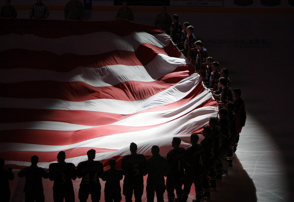 Photo - Hockey players and members of the military hold a giant American flag for military appreciation night at an AHL hockey game between the Oklahoma City Barons and the Grand Rapids Griffins at the Cox Convention Center in Oklahoma City, Saturday, March 24, 2012. Photo by Nate Billings, The Oklahoman