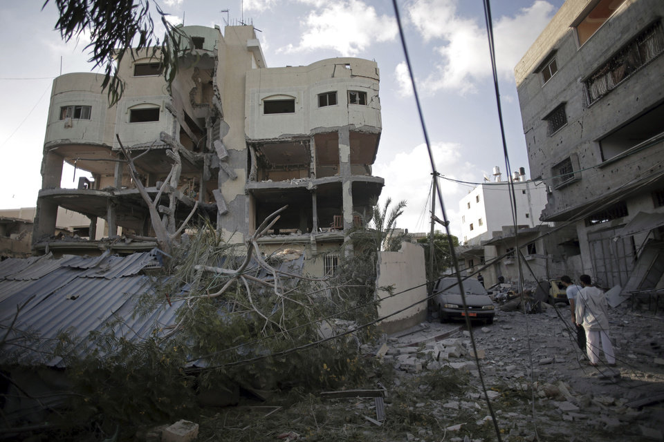 Photo - Palestinians inspect the damage to the house of Hamas leader, Mahmoud Zahar, following an early morning Israeli missile strike in Gaza City, Wednesday, July 16, 2014. Israel on Wednesday intensified air attacks on Hamas targets in the Gaza Strip following a failed Egyptian cease-fire effort, targeting the homes of four senior leaders of the Islamic militant movement and ordering tens of thousands of residents to evacuate border areas. (AP Photo/Khalil Hamra)