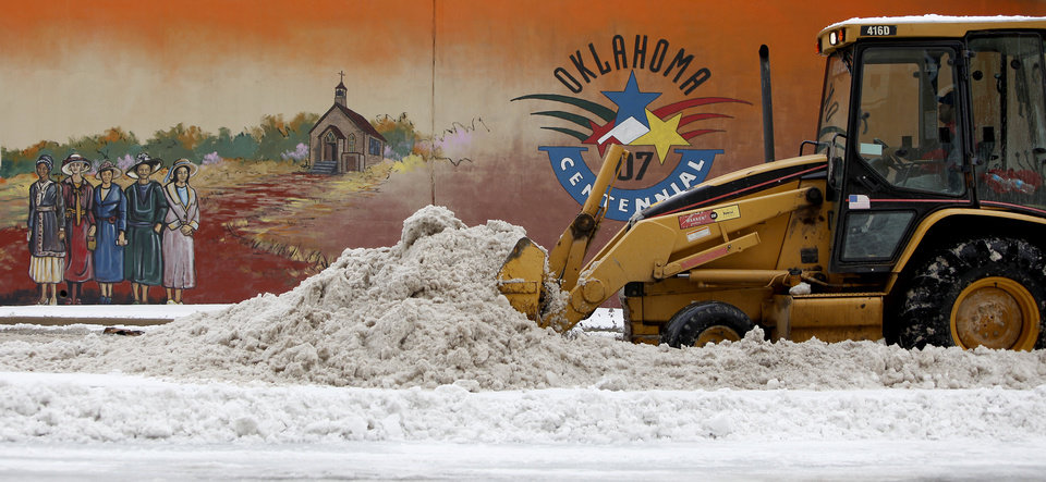 Photo - A front end loader clears snow on E.K. Gaylord Blvd in Oklahoma City, Saturday, Jan. 30, 2010.  Photo by Bryan Terry, The Oklahoman
