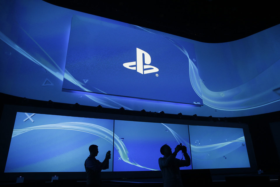 Photo - Attendees take pictures at  the Sony's Playstation presentation ahead of the Electronic Entertainment Expo on Monday, June 9, 2014, in Los Angeles. The spotlight at this week's E3 is expected to shift to games. (AP Photo/Jae C. Hong)