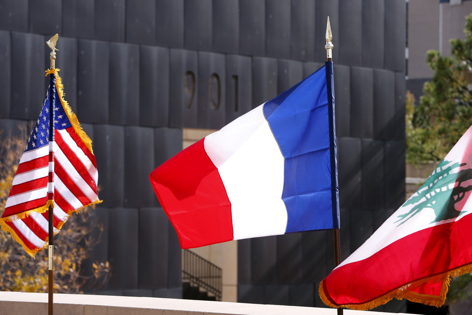 Photo - The flags of the United States of America, Republic of France and Lebanon fly as local and state officials and the Holocaust Remembrance and Restitution Foundation remember the victims of the Paris and Lebanon terrorist attacks at the Oklahoma City National Memorial & Museum's Survivor Tree on Tuesday, Nov. 17, 2015 in Oklahoma City, Okla.  Photo by Steve Sisney, The Oklahoman