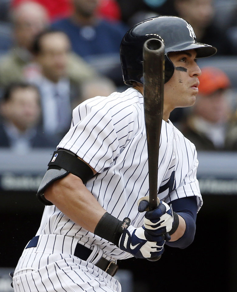 Photo - New York Yankees Jacoby Ellsbury hits a fifth-inning RBI single that scored Derekl Jeter in a baseball game during the Yankees home opener against the Baltimore Orioles, at Yankee Stadium in New York, Monday, April 7, 2014. (AP Photo/Kathy Willens)