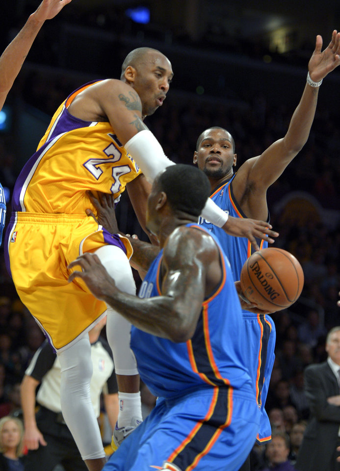 Los Angeles Lakers guard Kobe Bryant, left, passes between Oklahoma City Thunder forward Kevin Durant, back, and center Kendrick Perkins during the first half of their NBA basketball game, Friday, Jan. 11, 2013, in Los Angeles. (AP Photo/Mark J. Terrill) ORG XMIT: LAS107
