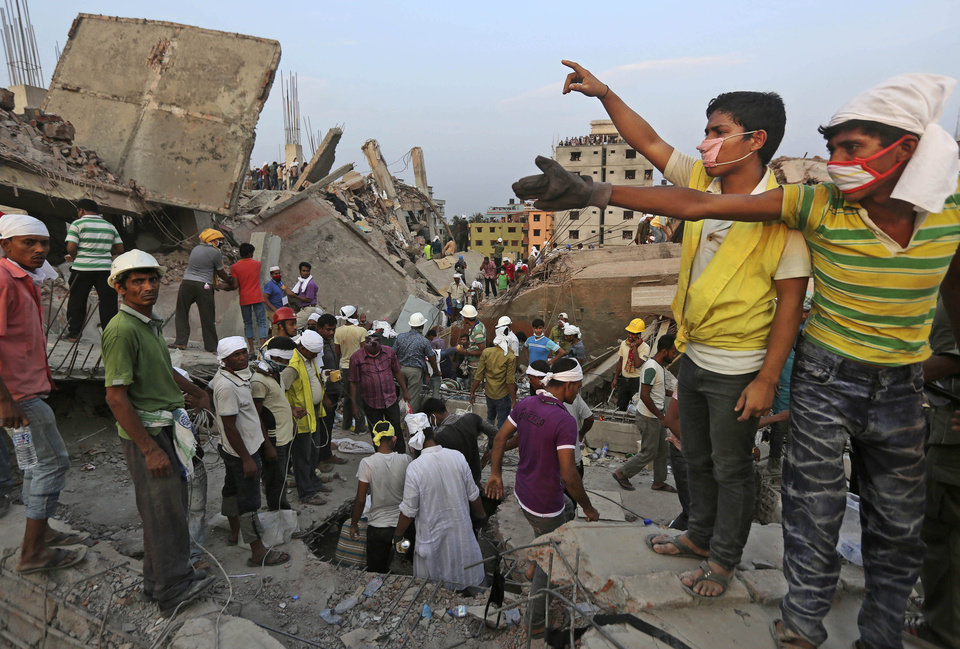 Photo - Bangladeshi rescuers from a youth group gesture for help at the site of a building that collapsed Wednesday in Savar, near Dhaka, Bangladesh, Thursday, April 25, 2013. By Thursday, the death toll reached at least 194 people as rescuers continued to search for injured and missing, after a huge section of an eight-story building that housed several garment factories splintered into a pile of concrete.(AP Photo/Kevin Frayer)