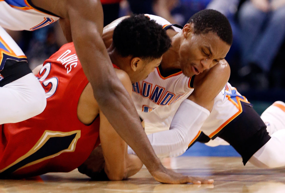 Photo - Thunder's Russell Westbrook (0) ties up Pelican's Anthony Davis (23) during the NBA basketball game between the Oklahoma City Thunder and the New Orleans Pelicans at Chesapeake Energy Arena on Dec. 21, 2014 in Oklahoma City, Okla. Photo by Steve Sisney, The Oklahoman