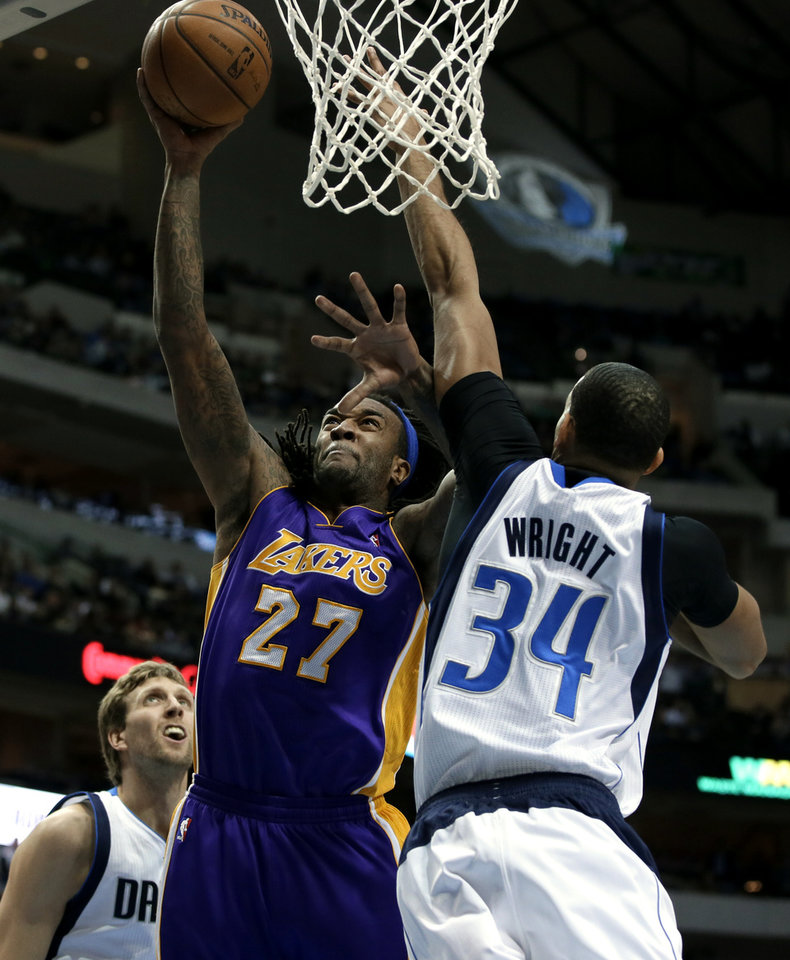 Photo - Los Angeles Lakers' Jordan Hill (27) goes up for a shot against Dallas Mavericks' Brandan Wright (34) as Dirk Nowitzki, left rear, watches in the first half of an NBA basketball game, Tuesday, Jan. 7, 2014, in Dallas. (AP Photo/Tony Gutierrez)