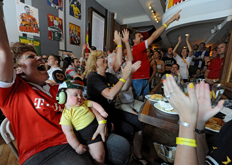 Photo - Eight-month-old Robert Hill, wearing headphones and a German beanie, is oblivious to the cheering from his grandmother Jo Loeffler, grandfather Mirko Loeffler, pointing at center,  and other soccer fans watching the broadcast of the World Cup soccer game between Germany and the United States. Fans of both teams were cheering at the end of the game, as both teams advanced. Mirko Loeffler is from Germany and was rooting for the German squad. (AP Photo/The Philadelphia Inquirer, Clem Murray)