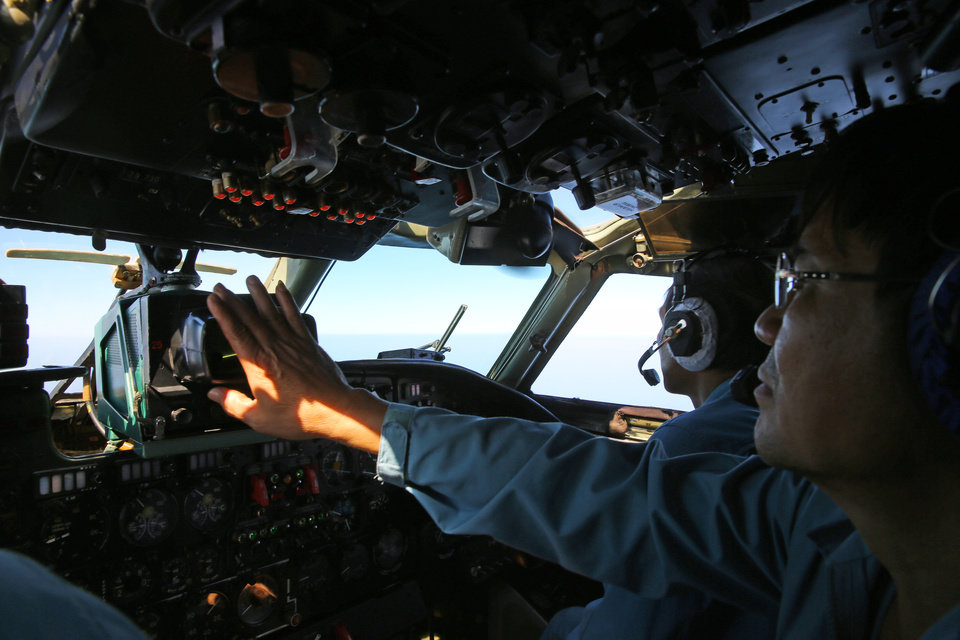 Photo - A cabin crew of the Vietnam Air Force is seen onboard a flying AN-26 Soviet made aircraft during a search operation for the missing Malaysia Airlines flight MH370 plane over the southern sea between Vietnam and Malaysia Friday, March 14, 2014. Vietnam says it has downgraded but not stopped its search for the missing jetliner in the South China Sea and has been asked by Malaysian authorities to consider sending planes and ships to the Strait of Malacca.  (AP Photo/Na Son Nguyen)