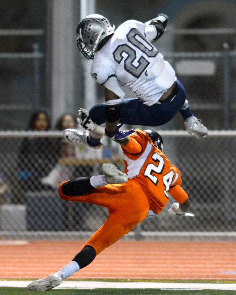 Freedom High\'s Joe Mixon (20) top, jumps over Pittsburg High\'s Deante Fortenberry (24) for a touchdown in the first quarter of their North Coast Section playoff football game in Pittsburg, Calif., on Friday, Nov. 22, 2013. (Doug Duran/Bay Area News Group)