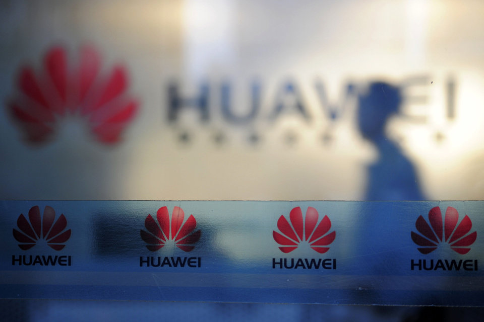 In this Monday, Oct. 8, 2012 photo, a man walks near company logos at a R&D center of Huawei Technologies Inc. in Wuhan, in central China's Hubei province. Eager to expand in the United States, China�s biggest technology companies face American anxiety about security and rising Chinese competition. (AP Photo) CHINA OUT