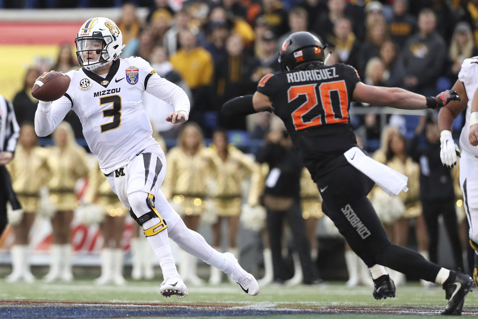 Photo - Missouri quarterback Drew Lock tries to escape the pocket as Oklahoma State safety Malcolm Rodriguez pursues during the first half of the Liberty Bowl NCAA college football game in Memphis, Tenn., Monday, Dec. 31, 2018. (Joe Rondone/The Commercial Appeal via AP)