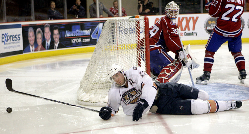 Photo - Oklahoma City's Josh Green falls in front of Hamilton's Peter Delmas during the AHL hockey game between the Oklahoma City Barons and the Hamilton Bulldogs at the Cox Convention Center in Oklahoma City, Tuesday, April 3, 2012. Photo by Sarah Phipps, The Oklahoman