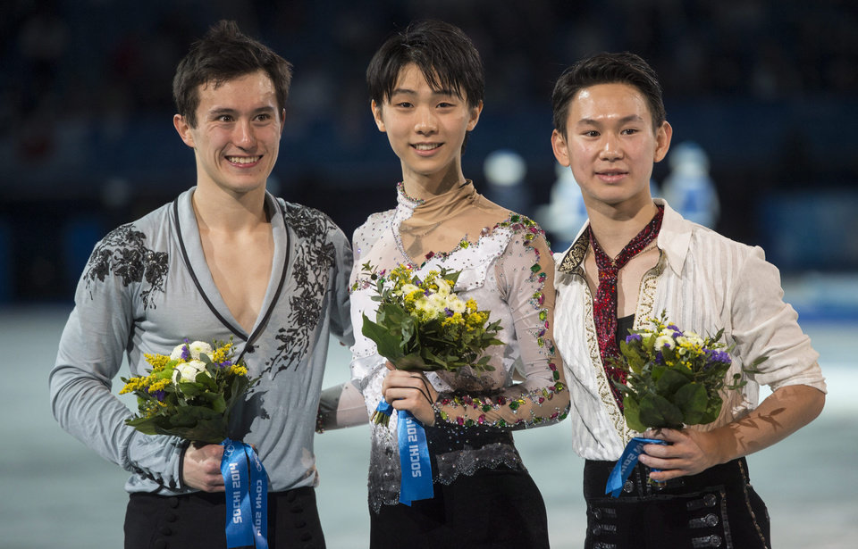Photo - Gold medalist Yuzuru Hanyu of Japan, center, silver medalist Patrick Chan of Canada, left, and bronze medalist Denis Ten of Kazakhstan, pose for photographs on the podium during the flower ceremony after the men's free skate figure skating final at the Iceberg Skating Palace during the 2014 Winter Olympics, Friday, Feb. 14, 2014, in Sochi, Russia. (AP Photo/The Canadian Press, Paul Chiasson)