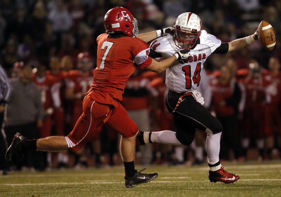 Claremore's Matt Whatley (14) runs from Carl Albert's Chevin Noone (7) during a high school football game between Carl Albert and Claremore in Midwest City, Friday, Nov. 16, 2012.  Photo by Garett Fisbeck, The Oklahoman