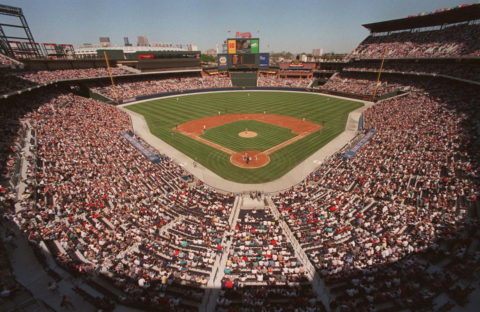Photo - FILE - This is a March 29, 1997 file photo of  baseball fans as they fill the stands as the Atlanta Braves play an exhibition game against the New York Yankess, the first baseball game ever to be played in the new Turner Field in Atlanta. Converting the Olympic Stadium to a baseball park helped to keep the Braves in downtown Atlanta. For athletes and spectators at Sochi, it's time to pack up. But for the host cities, the real challenge begins with the end of the Olympics. How do they continue to use the expensive stadiums after the party's over? What happens to the athletes' villages? What is the legacy of the games? After the 1996 games, the Olympics stadium was converted into Turner Field, the baseball stadium that's been home to the Atlanta Braves for the past several years (AP Photo/Ric Feld, File)