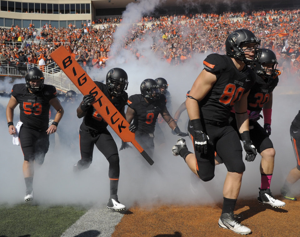 Photo -   Oklahoma State players take the field at the start of an NCAA college football game against TCU in Stillwater, Okla., Oct. 27, 2012. (AP Photo/Brody Schmidt)