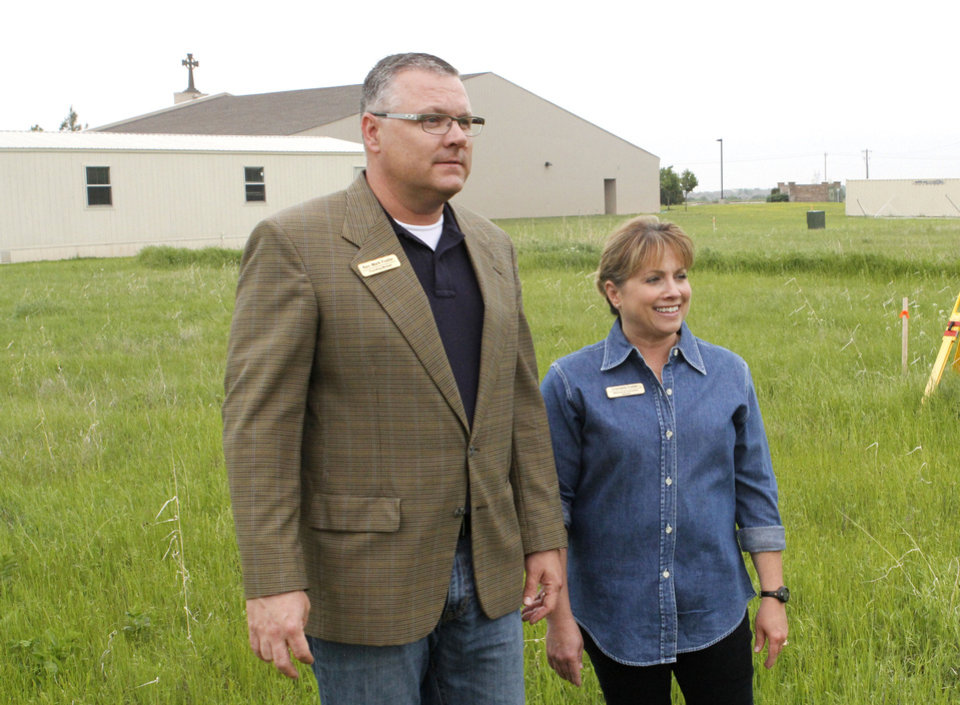 Photo - Rev. Mark Foster and Chantelle Foster look over the area where the Acts II United Methodist Church is preparing to build a new worship center in Edmond, OK, Friday, May 17, 2013,  By Paul Hellstern, The Oklahoman