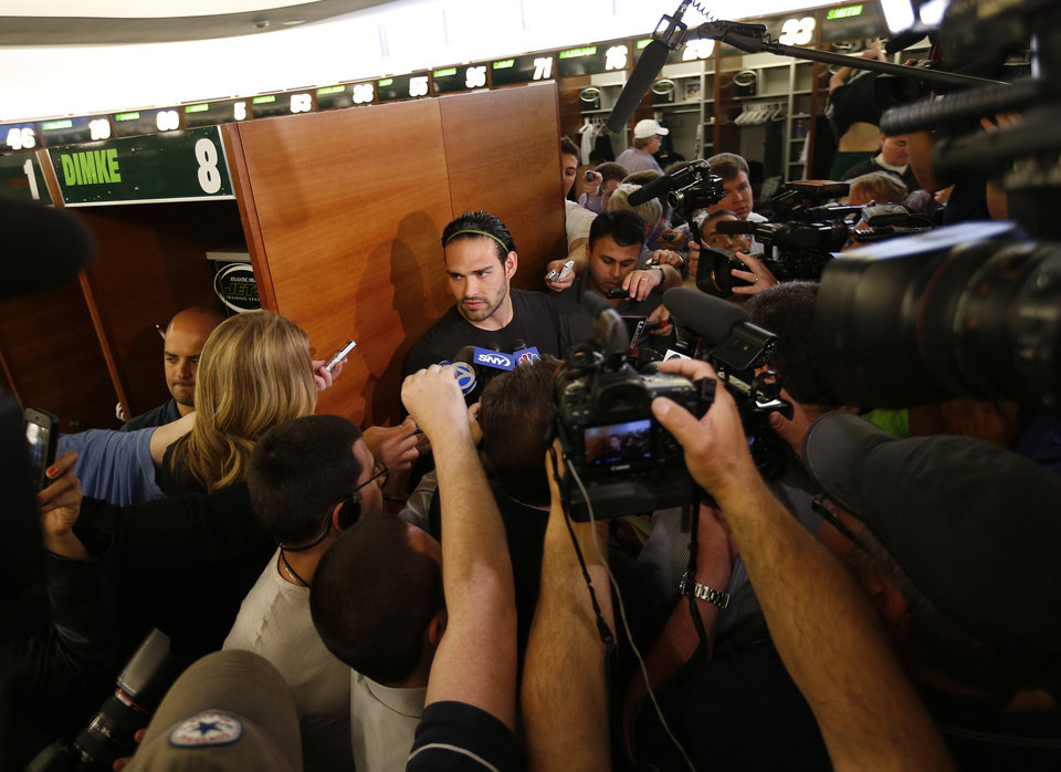 Photo - New York Jets quarterback Mark Sanchez, center, talks to reporters during a locker room availability at the team's NFL practice practice facility in Florham Park, N.J., Thursday, May 2, 2013. The Jets may have cut Tim Tebow but their situation at quarterback is far from settled. New general manager John Idzik says Sanchez, David Garrard, Greg McElroy, Matt Simms and second-round draft pick Geno Smith are all candidates to be the starter. (AP Photo/Rich Schultz)