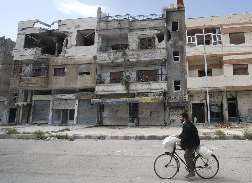 Photo -   In this picture taken during a UN observer-organized tour, a Syrian man rides his bicycle as he passes destroyed buildings in the Baba Amr neighborhood during the UN observers' visit to Homs city, central Syria, on Thursday, May 3, 2012. Syrian security forces stormed dorms at a northwestern university to break up anti-government protests there, killing at least four students and wounding several others with tear gas and live ammunition, activists and opposition groups said Thursday. (AP Photo/Muzaffar Salman)