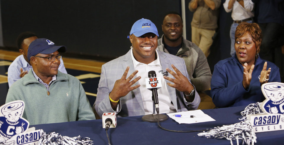 Photo - Casady High School football athlete Josh Wariboko-Alali puts on a UCLA hat during signing day ceremonies at Casady High School in Oklahoma City Wednesday, Feb. 4, 2015. At the table with him are his parents. Photo by Paul B. Southerland, The Oklahoman