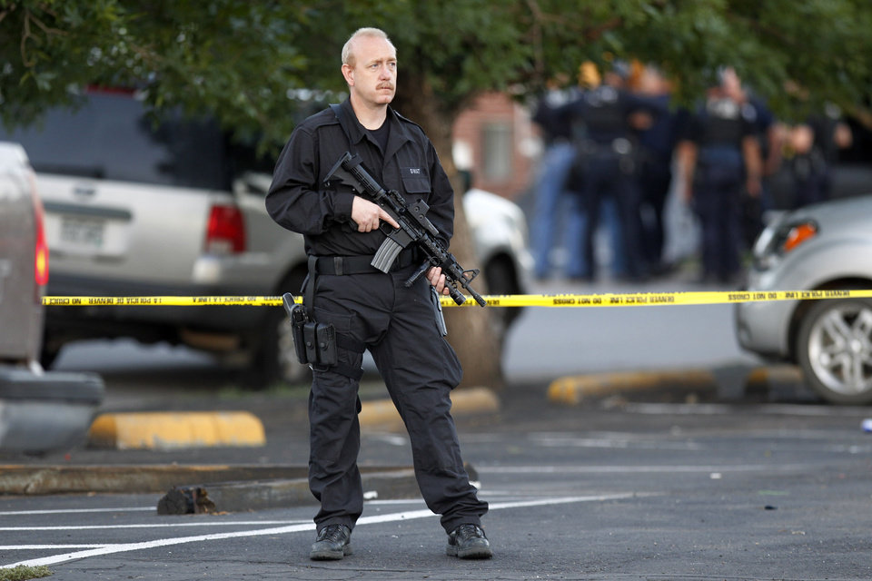 A SWAT team officer stands watch near an apartment house where the suspect in a shooting at a movie theatre lived in Aurora, Colo., Friday, July 20, 2012. As many as 14 people were killed and 50 injured at a shooting at the Century 16 movie theatre early Friday during the showing of the latest Batman movie. (AP Photo/Ed Andrieski) ORG XMIT: COEA108