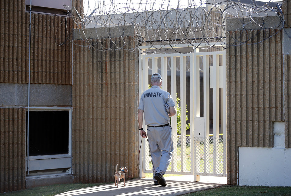 Photo -  Inmate Bill Miller leave the dog training area with Stanley at the Lexington Assessment and Reception Center, Friday, July 11,  2013, in Lexington, Okla. Photo by Sarah Phipps, The Oklahoman
