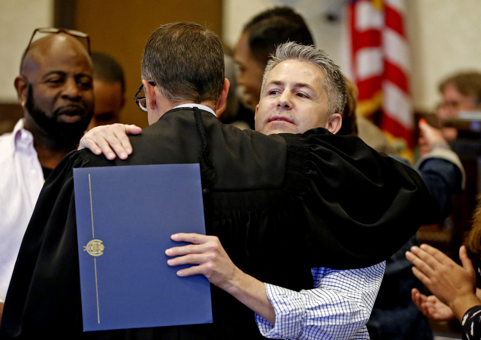 Photo -  Special Judge Michael Tupper hugs graduate Ronnie Hammond following Drug Court Graduation. [Photo by Steve Sisney, The Oklahoman]
