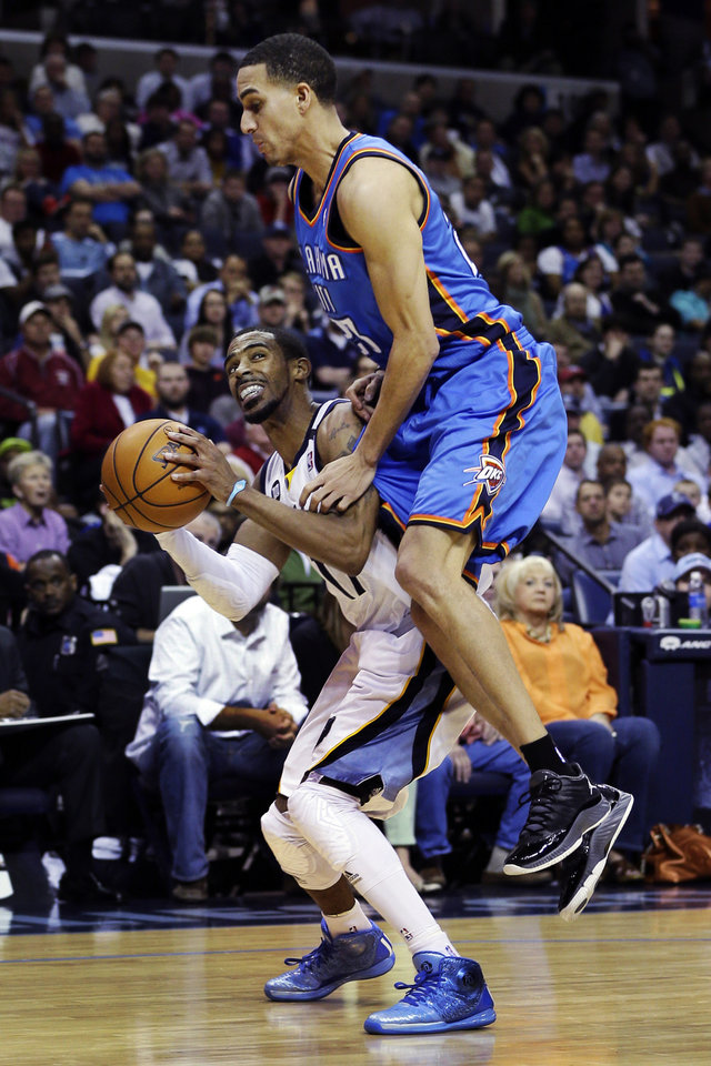 Photo - Memphis Grizzlies' Mike Conley, left, is fouled by Oklahoma City Thunder's Kevin Martin, top, during the second half of an NBA basketball game in Memphis, Tenn., Wednesday, March 20, 2013. The Grizzlies won 90-89 in overtime. (AP Photo/Danny Johnston) ORG XMIT: TNDJ108