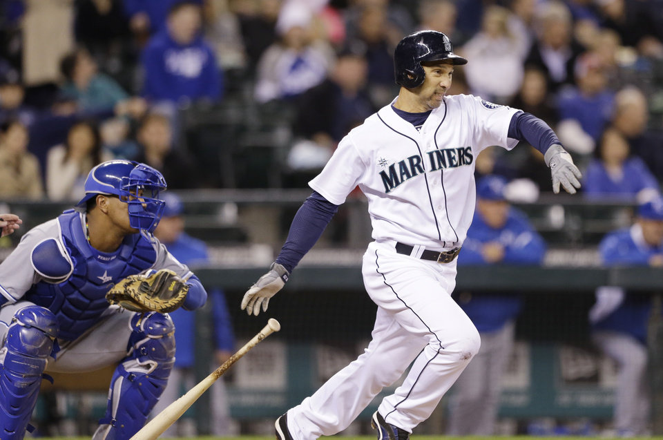 Photo - Seattle Mariners' Raul Ibanez, right, drops his bat as he takes off for first base as Kansas City Royals catcher Salvador Perez watches during the second inning of a baseball game Wednesday, Sept. 25, 2013, in Seattle. Ibanez grounded into a fielder's choice on the play; Kendrys Morales was out at second. (AP Photo/Elaine Thompson)