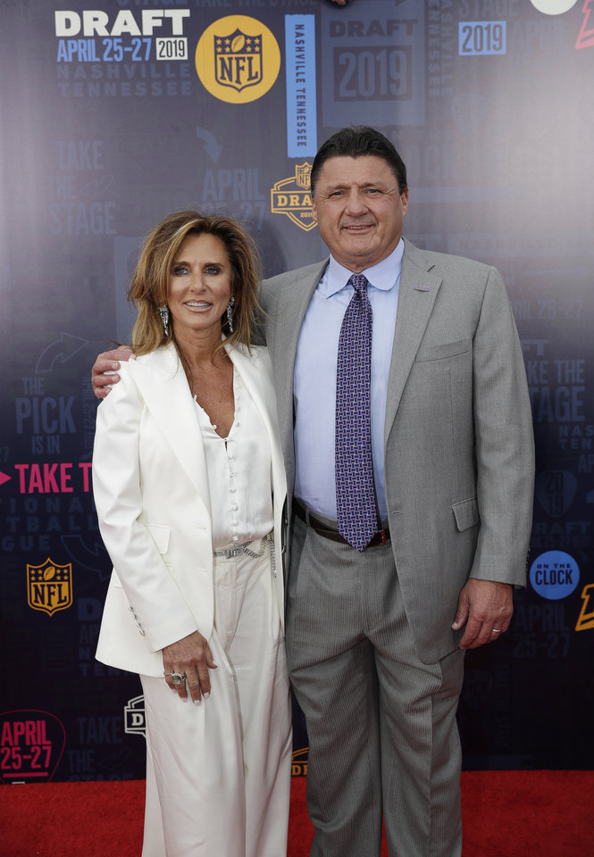 Photo - Louisiana State head coach Ed Orgeron and his wife Kelly walk the red carpet ahead of the first round at the NFL football draft, Thursday, April 25, 2019, in Nashville, Tenn. (AP Photo/Mark Humphrey)