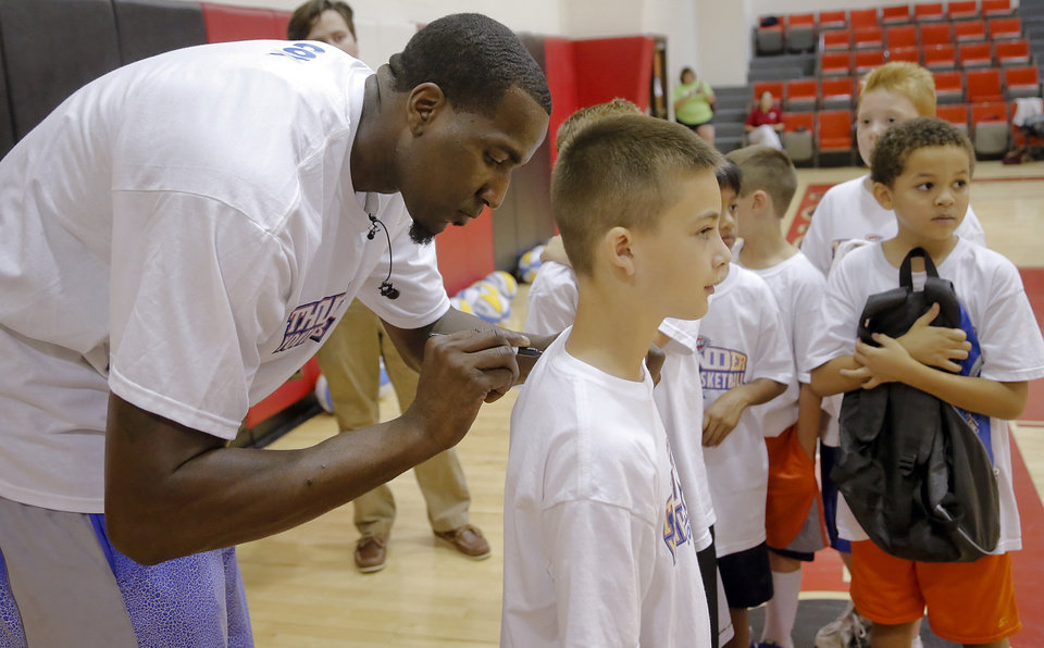 Oklahoma City Thunder's Kendrick Perkins signs the shirt of Brandon Herb as participants line up during the Oklahoma City Thunder basketball camp at Mid-America Christian University on Wednesday, June 19, 2013 in Oklahoma City, Okla.   Photo by Chris Landsberger, The Oklahoman