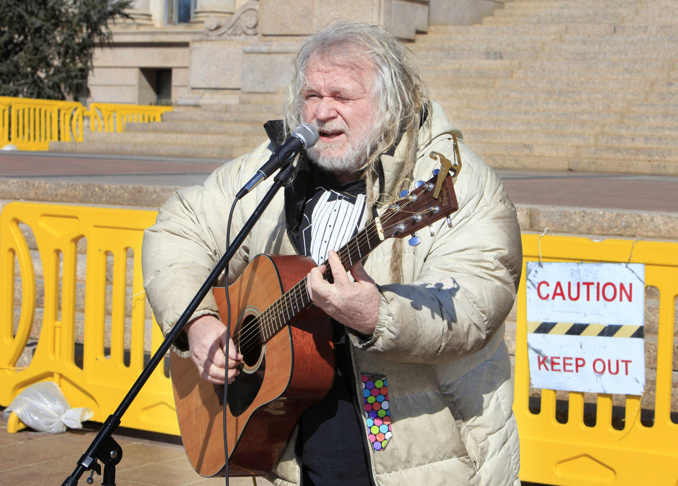 Photo - Bob Moore, Slaughterville, sings a song about marijuana in support of Senate Bill 2116 to legalize marijuana during a rally on the south steps of the state Capitol in Oklahoma City Wednesday, Feb. 12, 2014.  Supporters converged on the state Capitol to personally lobby their legislators to reform Oklahoma's strict marijuana laws during