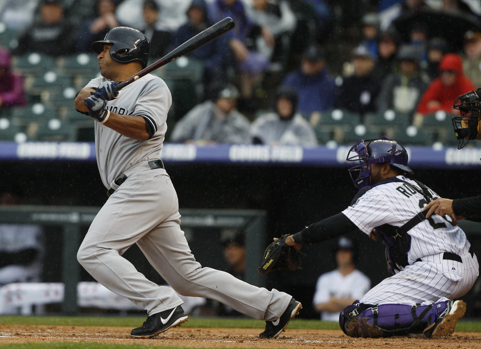 Photo - New York Yankees' Vernon Wells, left, hits an RBI-single as Colorado Rockies catcher Wilin Rosario looks on during the first inning of a baseball game in Denver on Thursday, May 9, 2013. (AP Photo/David Zalubowski)