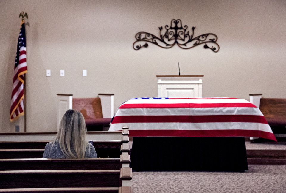 Photo -  A person pays respects Wednesday before the start of the funeral of homeless Army veteran William Eugene Weeks Jr., 64, at Chapel Hill Funeral Home in Oklahoma City. [Photo by Chris Landsberger, The Oklahoman]