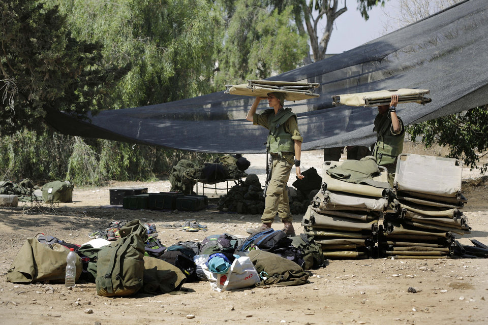 Photo - Israeli soldiers carry a bunk beds near the Israel Gaza border, Israel, Monday, July 7, 2014. The Islamic militant group Hamas that rules Gaza vowed revenge on Israel for the death of several of its members killed in an airstrike early Monday morning in the deadliest exchange of fire since the latest round of attacks began weeks ago. (AP Photo/Tsafrir Abayov)