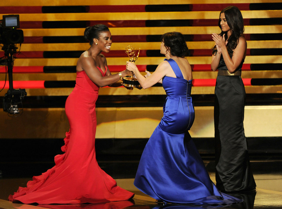 "Photo - Uzo Aduba, left, presents the award for outstanding directing for a comedy series to Gail Mancuso for her work on ""Modern Family"" at the 66th Annual Primetime Emmy Awards at the Nokia Theatre L.A. Live on Monday, Aug. 25, 2014, in Los Angeles. (Photo by Chris Pizzello/Invision/AP)"