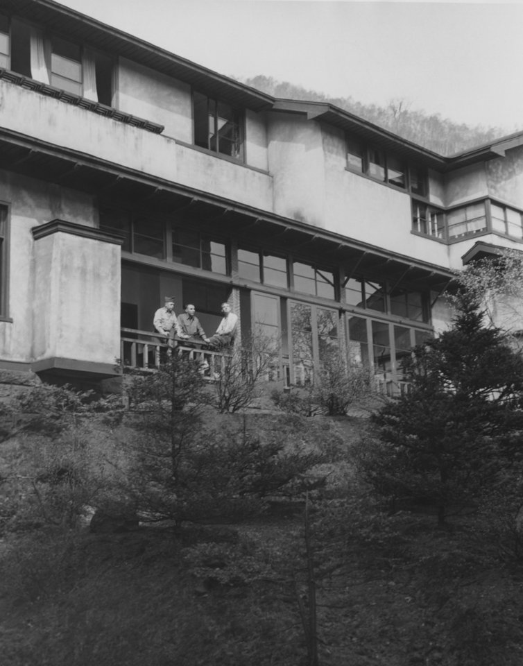 """Photo - Perched high in the volcanic mountains of southern Hokkaido, Noboribetsu's Grand hotel offers three days of 'story book living' to hardworking 45th Infantry division Thunderbirds.  The hotel's four wings are built around a terraced patio.  Pausing on their way to an early morning mineral bath on the balcony railing are Cpl. J. Cordle, Atlanta, Ga.; Pfc. Anthony Domaratz, Cheswick, Pa, ; and Pfc. Donald Fichter, Landsing, Mich.""""  Photo by Ron Pyer of 45th Division News Photo.  Entered the library 06/08/1951."""