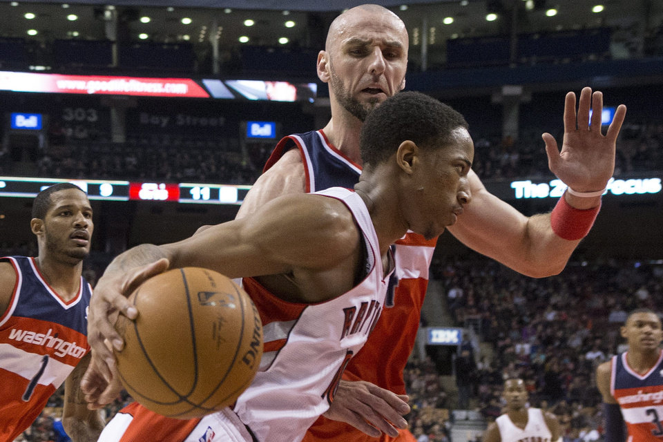 Photo - Toronto Raptors' DeMar DeRozan drives past Washington Wizard's Marcin Gortat during first half NBA basketball action in Toronto, Thursday, Feb. 27, 2014. (AP Photo/The Canadian Press, Chris Young)