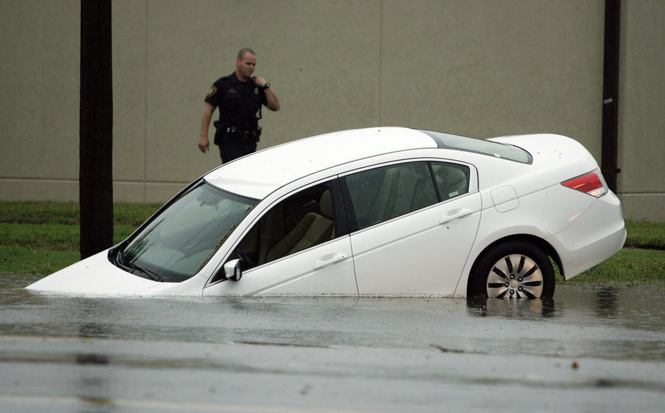 A driver attempting to turn onto West Lindsay Street had to be extracted from this vehicle during heavy thunderstorms in Norman, Okla. on Wednesday, April 29, 2009.   Photo by Steve Sisney, The Oklahoman