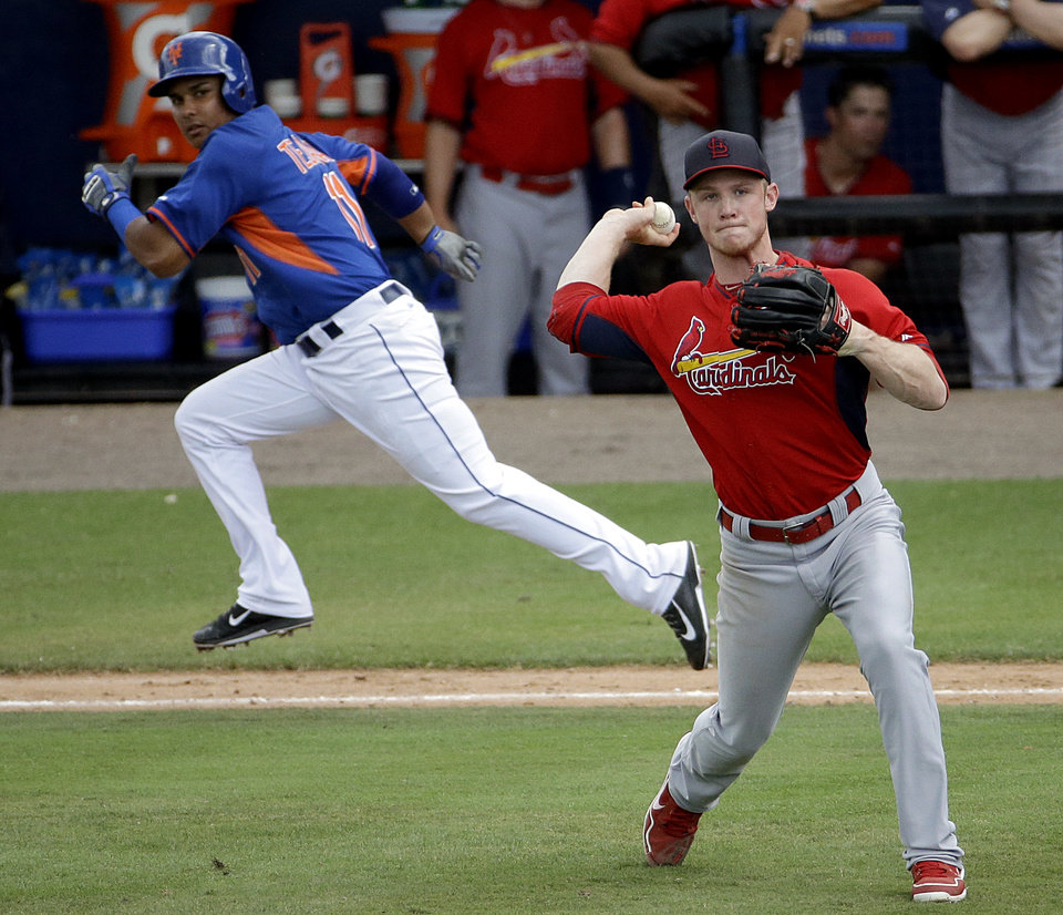 Photo - St. Louis Cardinals relief pitcher Keith Butler, right, throws to third base to get out New York Mets' Taylor Teagarden after fielding a bunt by Ruben Tejada, left, in the seventh inning of an exhibition spring training baseball game, Wednesday, March 12, 2014, in Port St. Lucie, Fla. (AP Photo/David Goldman)