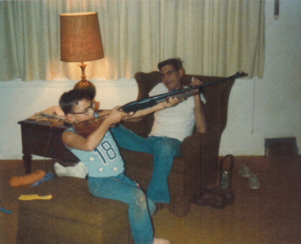 Photo -  Jim wielding what looks to be a shotgun inside his family's house as his father looks on.