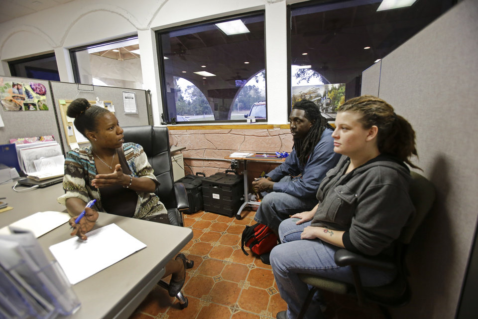 Photo - In this Tuesday, April 8, 2014 photo, Community Hope Center caseworker Mia Brennon, left, helps in finding Anthony and Candice Johnson housing in Kissimmee, Fla. (AP Photo/John Raoux)